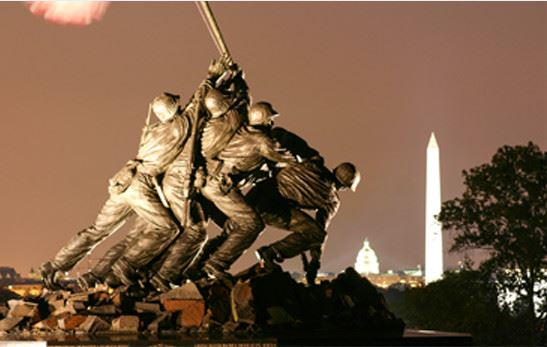 Marine Corps Memorial with spotlight shining on it at night